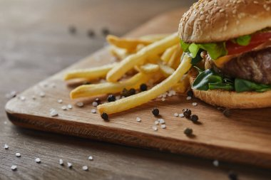 golden french fries with tasty meat burger with scattered salt and black pepper on wooden chopping board