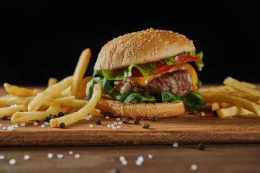 golden french fries with tasty meat burger with scattered salt and black pepper on wooden chopping board isolated on black