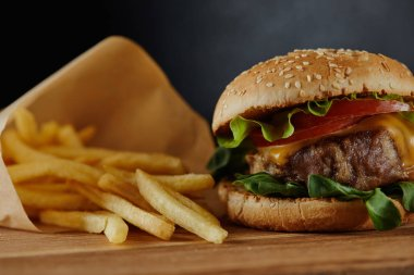 delicious burger with meat and french fries on wooden surface