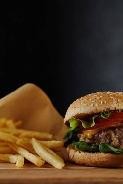 selective focus of delicious burger with meat and french fries on black background
