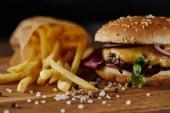 selektivní zaměření soli, hranolky a vynikající Burger s masem na dřevěném povrchu