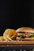 selektivní zaměření soli, hranolky a lahodný Burger s masem na dřevěném povrchu izolovaného na černém