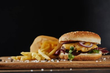 salt, french fries and delicious burger with meat on wooden surface isolated on black