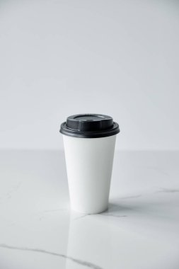 white disposable cup with black cap on white marble surface isolated on grey