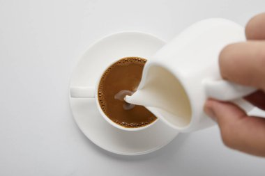 Cropped view of woman pouring milk in coffee on white