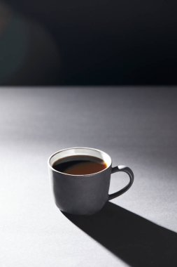 Cup of coffee on grey surface on black