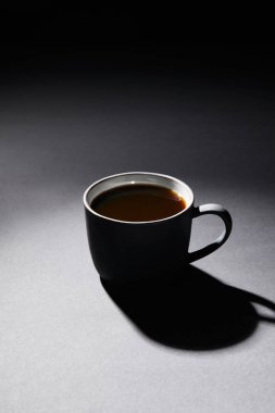 Full cup of coffee on dark textured surface