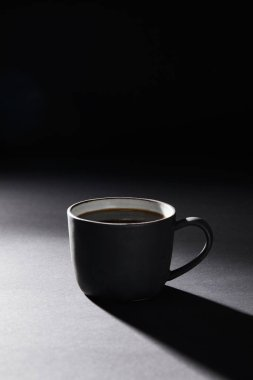 Coffee cup on dark textured surface on black