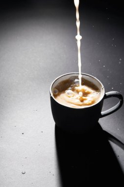 Cup of coffee with pouring milk on dark textured surface