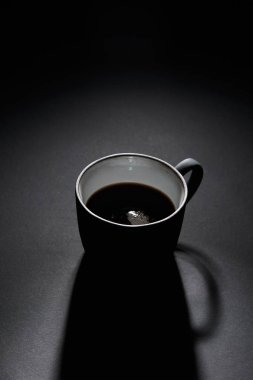 Cup of black coffee on dark textured surface