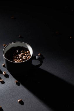 Coffee cup and coffee grains on dark textured surface