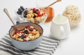 bowl on striped napkin with oat flakes, nuts and berries on white table with milk jug