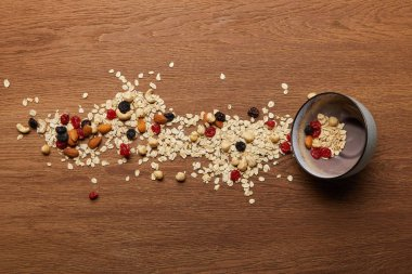 top view of oat flakes scattered with nuts and dried berries near bowl at wooden table
