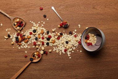 top view of oat flakes scattered with nuts and dried berries near bowl and spoons at wooden table