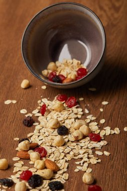 oat flakes scattered with nuts and dried berries from bowl on wooden table