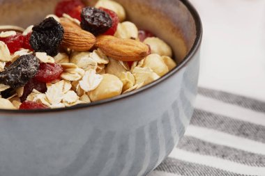 close up of bowl with muesli on striped napkin