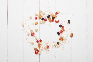 top view of scattered dried berries, oat flakes and nuts on white wooden table