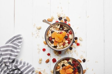 top view of bowls with muesli, dried apricots and berries and nuts served for breakfast with scattered ingredients on white wooden table