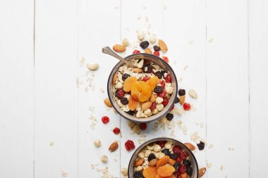 top view of bowls with muesli, dried apricots and berries and nuts served for breakfast with scattered ingredients on white table