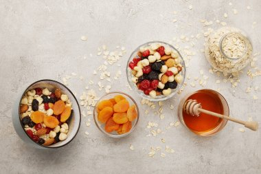 top view of bowls with muesli, dried apricots and berries, nuts and honey on textured grey surface with messy scattered oat flakes