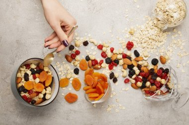 cropped view of woman holding spoon near bowls with muesli, dried apricots and berries, nuts on textured grey surface with messy scattered ingredients