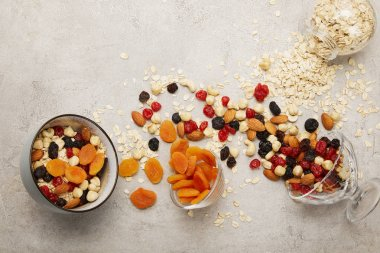 top view of bowls with muesli, dried apricots and berries, nuts on textured grey surface with messy scattered ingredients