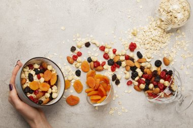 cropped view of woman holding bowl with muesli, dried apricots and berries, nuts on textured grey surface with messy scattered ingredients