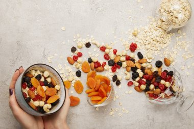 partial view of woman holding bowl with muesli, dried apricots and berries, nuts on textured grey surface with messy scattered ingredients