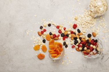 top view of oat flakes, dried apricots and berries, nuts messy scattered on textured grey surface
