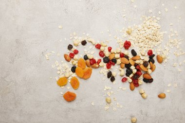 top view of oat flakes, dried apricots and berries, nuts messy scattered on textured grey surface table
