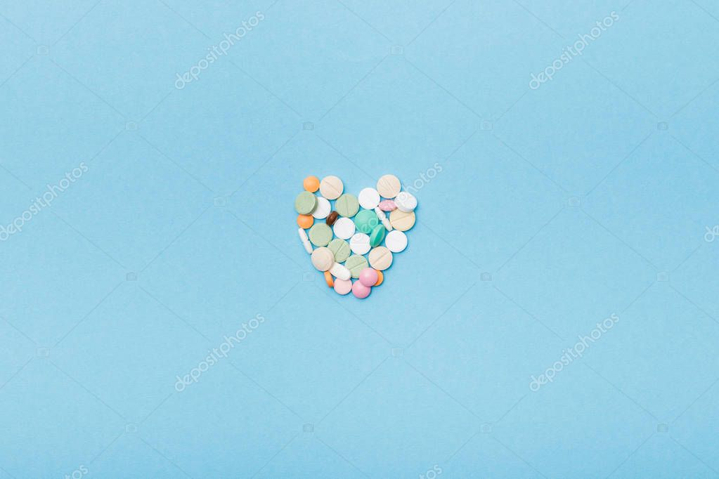 Flat lay with colorful pills on blue surface