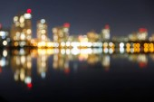 rozostřený tmavý panoráma s osvětleným stavbami, reflexním a bokehem v noci