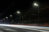 Dlouhá expozice světel na pozemních komunikacích v noci u osvětlených budov