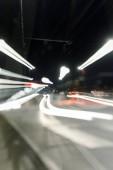 Dlouhá expozice světlých světel na rušné silnici v noci ve městě
