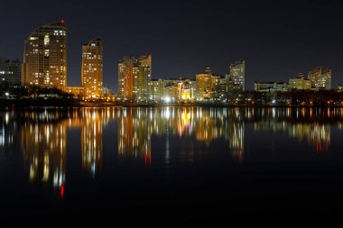 dark cityscape with illuminated buildings with reflection on water at night