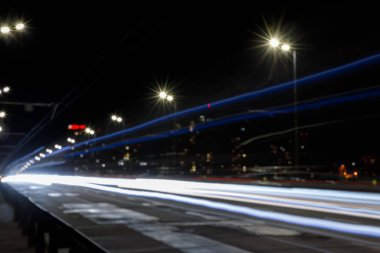 Long exposure of lights on road at nighttime near illuminated buildings stock vector