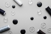 Fotografia top view of clothing buttons and thread coils isolated on grey