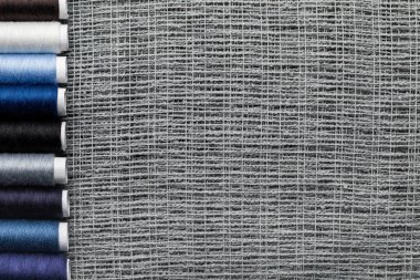top view of blue and grey thread coils in row on sackcloth with copy space