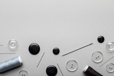 top view of clothing buttons, needles and thread coils isolated on grey with copy space