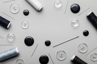 top view of black and transparent clothing buttons, needles and thread coils isolated on grey