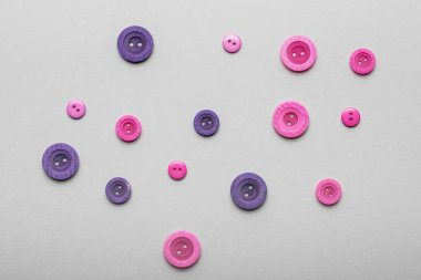 Top view of pink and violet clothing buttons isolated on grey stock vector