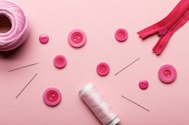 top view of clothing buttons, thread coil and sewing supplies isolated on pink