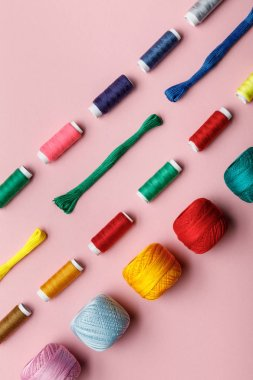 top view of colorful knitting yarn balls, embroidery threads and thread coils on pink