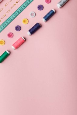 top view of colorful thread coils, buttons and sewing supplies isolated on pink with copy space
