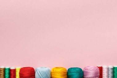 top view of arranged colorful cotton knitting yarn balls and thread coils isolated on pink with copy space