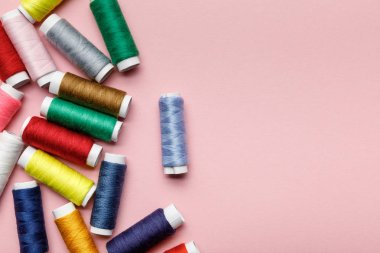 top view of scattered colorful thread coils isolated on pink with copy space