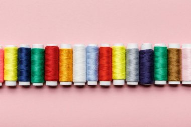 top view of colorful thread coils in row on pink