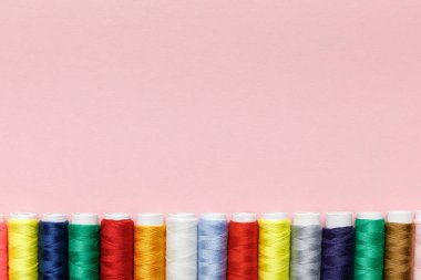 top view of colorful thread coils in row isolated on pink with copy space