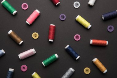 top view of colorful thread coils with various buttons isolated on black