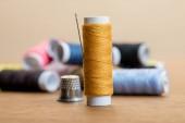 selektiver Fokus der Baumwollfadenspule mit Nadel isoliert auf beige